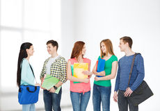 Group of smiling students standing. Education and people concept - group of smiling students with bags and folders having discussion Royalty Free Stock Images