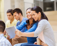 Group of smiling students with tablet pc Stock Images