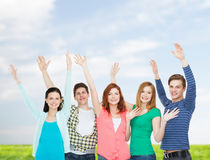 Group of smiling students waving hands Stock Photo