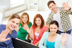 Group of smiling students waving hands at school. Education, technology, school and people concept - group of smiling students waving hands in computer class at Stock Photos