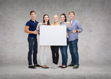Group of smiling students with white blank board Stock Photo