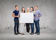 Group of smiling students with white blank board Royalty Free Stock Photo