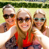 Group of smiling teen girls taking selfie in park