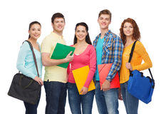 Group of smiling teenagers. Friendship, youth, education and people concept - group of smiling teenagers with folders and school bags Royalty Free Stock Image
