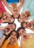 Group of smiling teenagers. Friendship, youth, gesture and people - group of smiling teenagers in circle shouting Royalty Free Stock Photos
