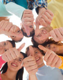 Group of smiling teenagers. Friendship, youth, gesture and people - group of smiling teenagers in a circle showing thumbs up Royalty Free Stock Image