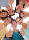 Group of smiling teenagers. Friendship, youth, gesture and people - group of smiling teenagers in a circle showing thumbs up Royalty Free Stock Photography