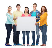 Group of smiling teenagers. Friendship, youth and people - group of smiling teenagers with big white blank billboard Royalty Free Stock Photos