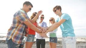 Group of smiling teenagers hanging out outdoors stock footage