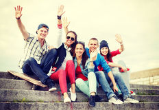 Group of smiling teenagers hanging out. Summer holidays and teenage concept - group of smiling teenagers hanging outside and waving hands Stock Image