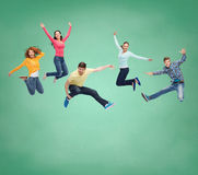 Group of smiling teenagers jumping in air Stock Photos