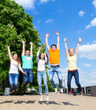 Group of smiling teenagers jumping outdoors Stock Photo