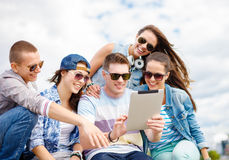 Group of smiling teenagers looking at tablet pc Stock Photo