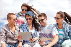 Group of smiling teenagers looking at tablet pc Stock Images