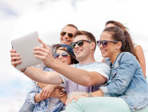Group of smiling teenagers looking at tablet pc Royalty Free Stock Photography