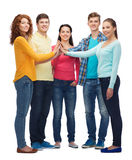 Group of smiling teenagers making high five. Friendship, youth, gesture and people - group of smiling teenagers making high five Stock Photos