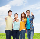 Group of smiling teenagers over blue sky and grass Stock Photo