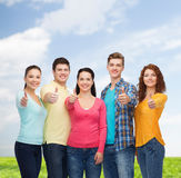 Group of smiling teenagers over blue sky and grass Royalty Free Stock Photos