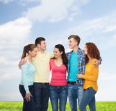 Group of smiling teenagers over blue sky and grass Royalty Free Stock Image