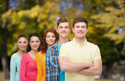 Group of smiling teenagers over green park Stock Photos