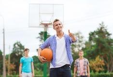 Group of smiling teenagers playing basketball Stock Image
