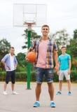 Group of smiling teenagers playing basketball Stock Photos