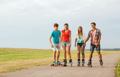 Group of smiling teenagers with roller-skates Stock Images