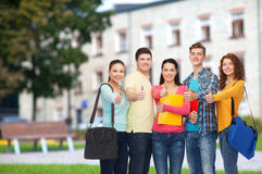 Group of smiling teenagers showing thumbs up Stock Images