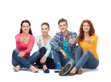 Group of smiling teenagers showing thumbs up Stock Image