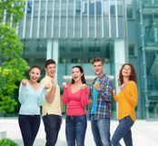 Group of smiling teenagers showing triumph gesture Stock Images