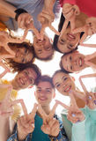 Group of smiling teenagers showing victory sign. Friendship, youth, gesture and people - group of smiling teenagers in circle showing victory sign Stock Photo