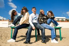 Group smiling teenagers sitting on a bench. Five teenage friends sitting on a bench at the seaside Royalty Free Stock Photo