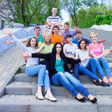 Group of smiling teenagers sitting on the stairs Royalty Free Stock Images