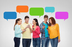 Group of smiling teenagers with smartphones. Friendship, technology, communication and people concept - group of smiling teenagers with smartphones over Royalty Free Stock Photo