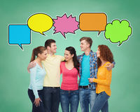 Group of smiling teenagers with text bubbles. School, education, communication and people concept - group of smiling teenagers over green board background with Stock Photos