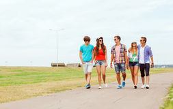 Group of smiling teenagers walking outdoors Royalty Free Stock Images