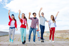 Group of smiling teenagers waving hands Royalty Free Stock Photos
