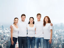 Group of smiling teenagers in white blank t-shirts Stock Image