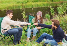 Group of smiling tourists drinking beer in camping Stock Image
