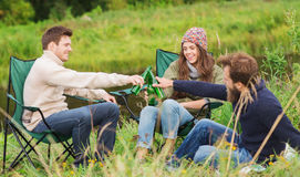 Group of smiling tourists drinking beer in camping Stock Images