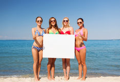Group of smiling women with blank board on beach Stock Images