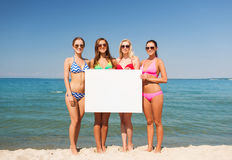 Group of smiling women with blank board on beach Stock Photos