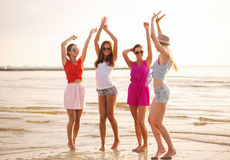 Group of smiling women dancing on beach stock photo