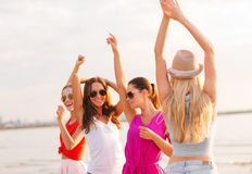 Group of smiling women dancing on beach. Summer vacation, holidays, travel and people concept - group of smiling young women in sunglasses and casual clothes royalty free stock image