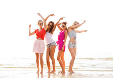 Group of smiling women dancing on beach. Summer vacation, holidays, travel and people concept - group of smiling young women in sunglasses and casual clothes royalty free stock photo