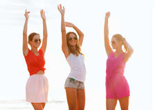 Group of smiling women dancing on beach. Summer vacation, holidays, travel and people concept - group of smiling young women in sunglasses and casual clothes stock images