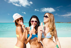 Group of smiling women eating ice cream on beach Stock Photography
