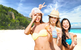Group of smiling women eating ice cream on beach. Summer holidays, vacation, food, travel and people concept - group of smiling young women eating ice cream over Royalty Free Stock Photography