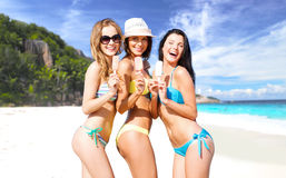 Group of smiling women eating ice cream on beach Stock Photo