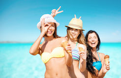 Group of smiling women eating ice cream on beach. Summer holidays, vacation, food, travel and people concept - group of smiling young women eating ice cream on stock photography